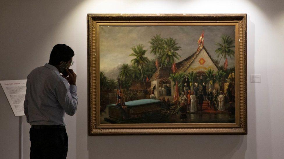 A man on the phone looks at Raja Ravi Varma's paining