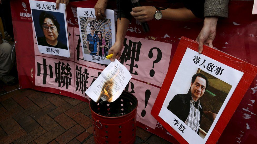 A pro-democracy demonstrator burns a letter next to pictures of missing staff members of a publishing house and a bookstore, including Gui Minhai, a China-born Swedish national who is the owner of Mighty Current, Cheung Jiping, the business manager of the publishing house and Causeway Bay Books shareholder Lee Bo (L-R), during a protest to call for an investigation behind their disappearance, outside the Chinese liaison office in Hong Kong, China January 3, 2016