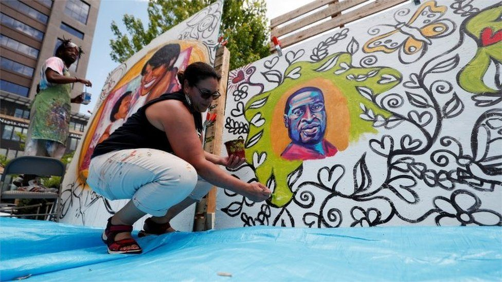 A woman paints a memorial to George Floyd on the anniversary of his murder