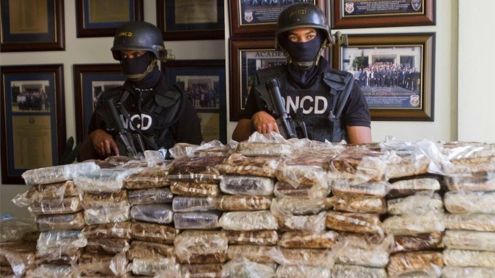 Dominican police officers show some of the cocaine seized on board the plane