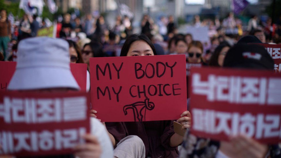 Protesters hold placards reading 'Abolish punishment for abortion' as they protest South Korean abortion laws in Gwanghwamun plaza in Seoul on July 7, 2018