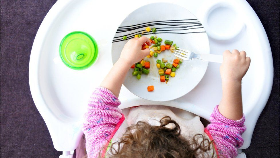 Above view of a little toddler child eats vegetables.