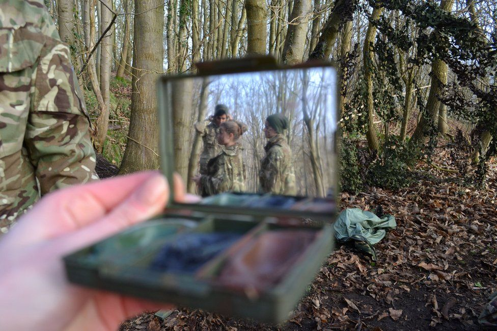 A view of women in camouflage seen in a mirror.