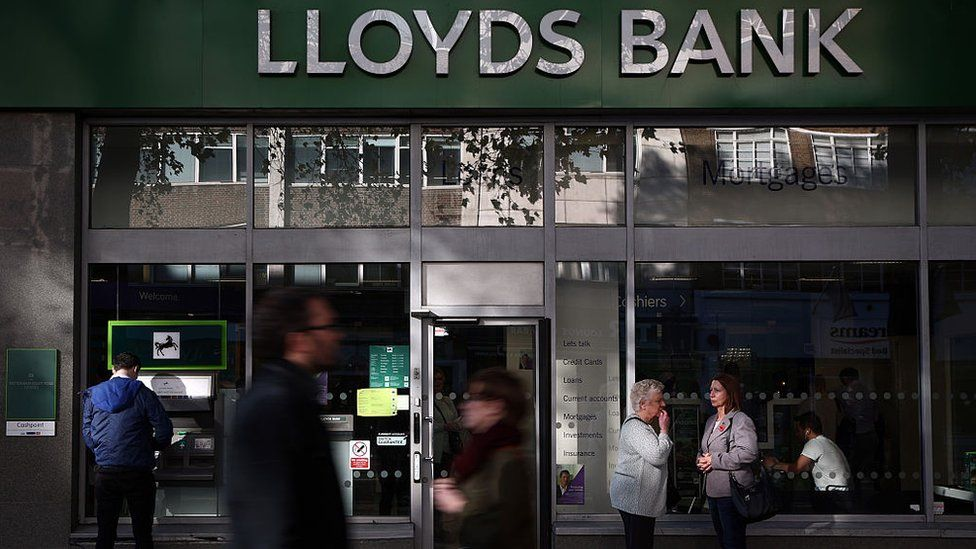 People stand outside or walk past a Lloyds bank branch