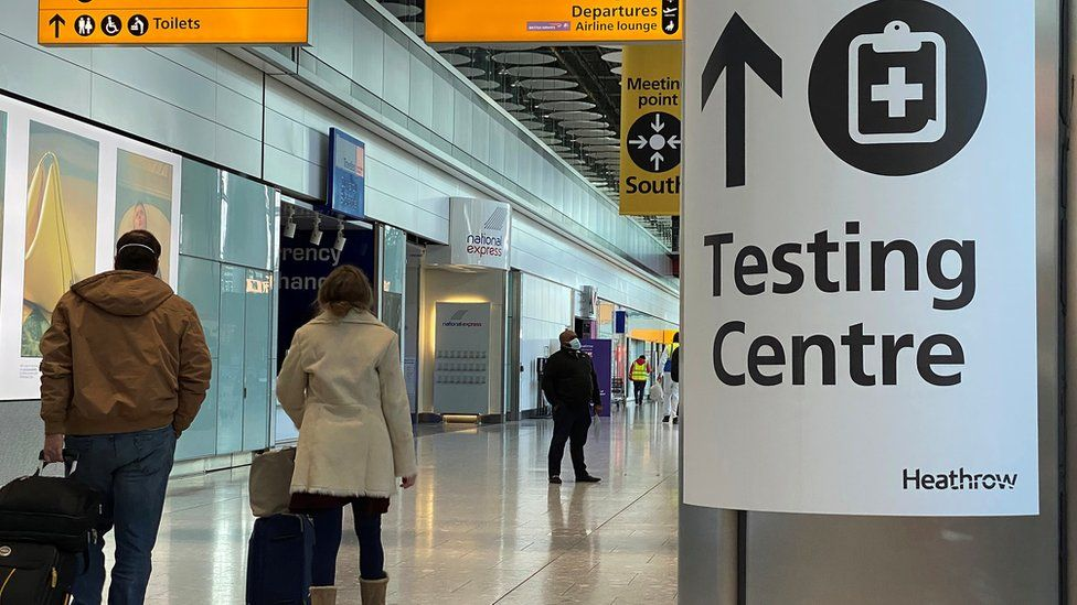 Travellers walking past a testing centre sign at Heathrow Airport
