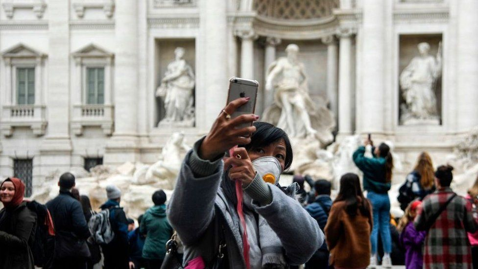 A Chinese tourist by the Trevi fountain in Rome, taking a selfie while wearing a face mask