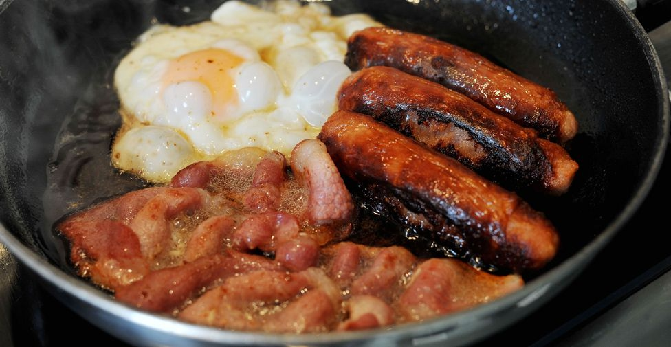 Bacon, egg and sausages frying in a pan