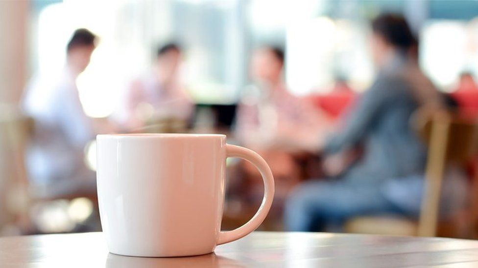 Coffee cup and people meeting in the background