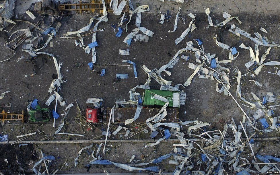 An aerial picture shows damaged trucks and a shipping container near the site of explosions, in Tianjin, China, on 15 August, 2015