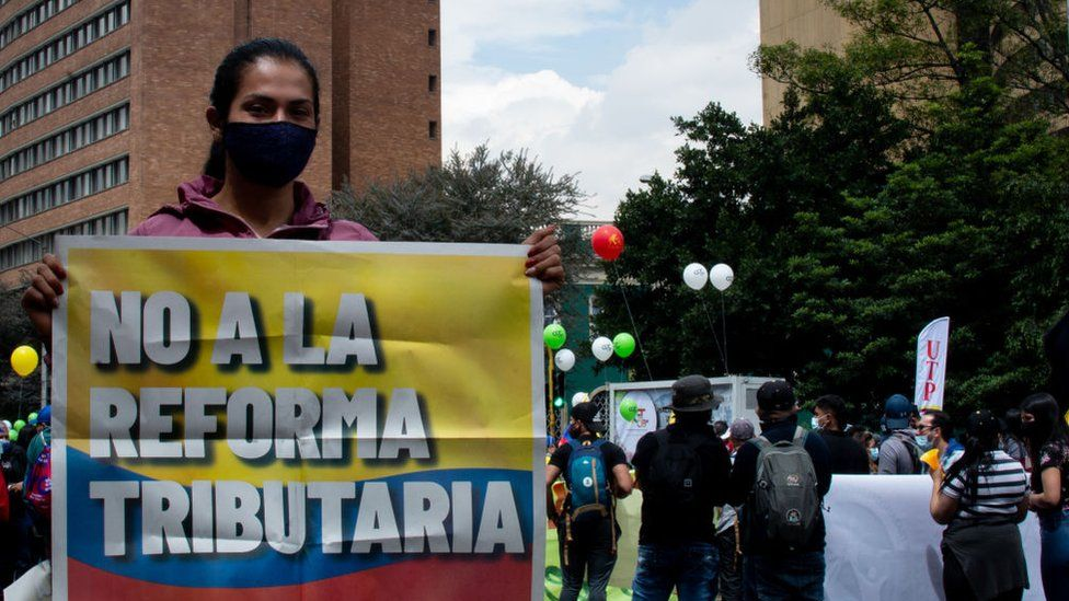 A woman holds sign opposing the tax reform in Bogota, Colombia on April 28, 2021.