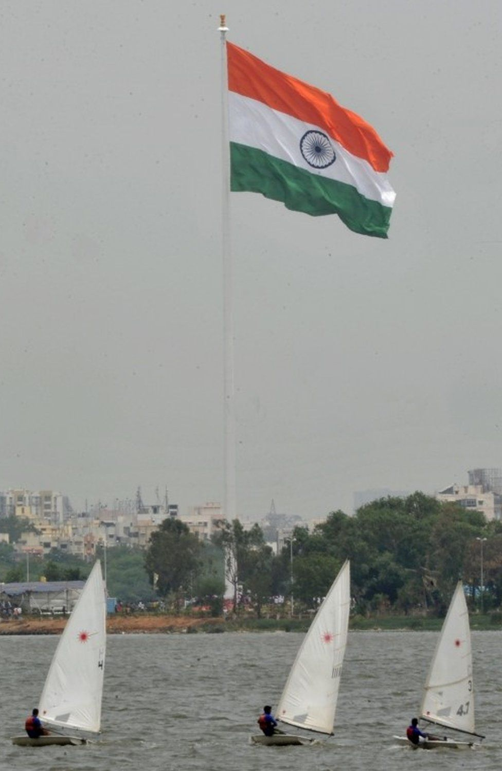 Indians sail boats as an Indian Tricolour flag flutters on an 83 metre (272.31 feet) flagpole after being unfurled during a ceremony to mark the Second Telangana State Formation Day at Sanjeevaiah Park on the banks of the Hussainsagar Lake in Hyderabad on June 2, 2016. T