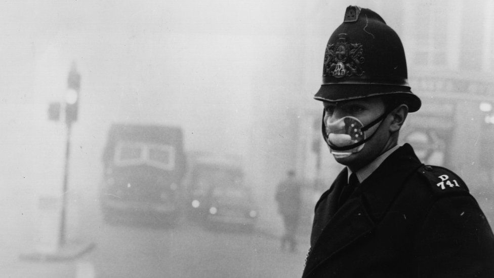 A policeman in London wearing a mask amid thick smog in 1962