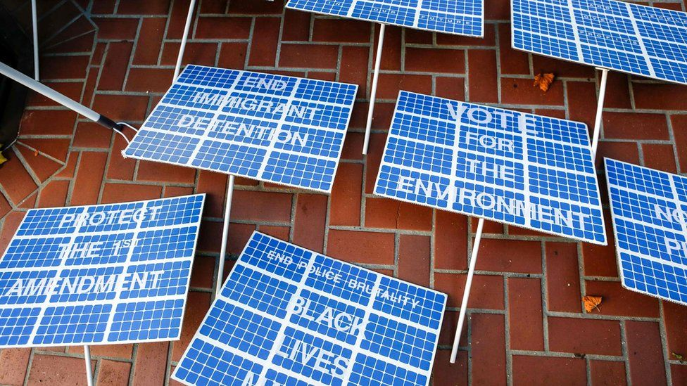 """Signs designed to resemble solar panels lie on the sidewalk before the """"Rise For Climate"""" march in downtown San Francisco, California on 8 September 2018."""