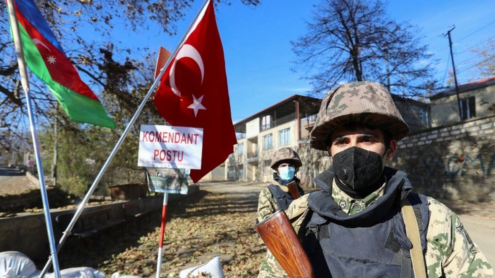 Azeri service members stand guard near state flags of Azerbaijan and Turkey at a checkpoint in Hadrut town on 26 November