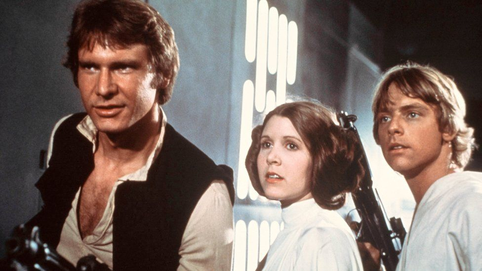 From left to right: Harrison Ford, Carrie Fisher, and Mark Hamill are shown in a scene from Star Wars