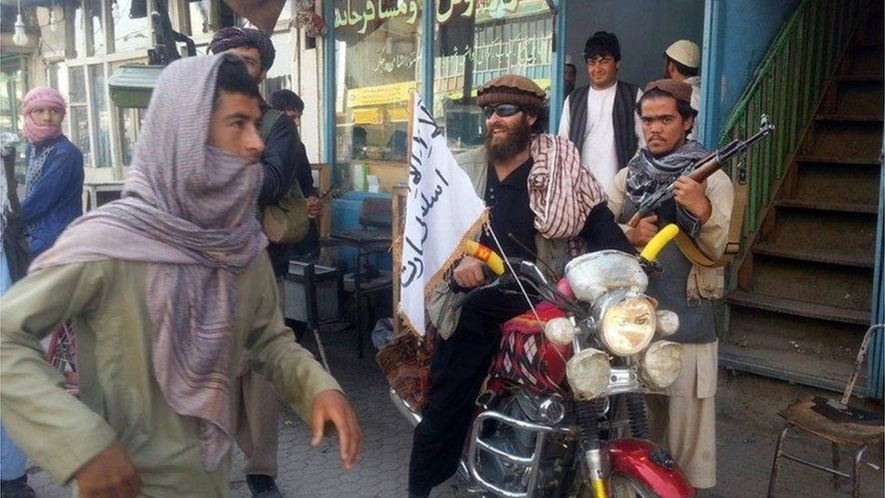 In this Tuesday, Sept. 29, 2015 file photo, a Taliban fighter sits on his motorcycle adorned with a Taliban flag in a street in Kunduz, Afghanistan.