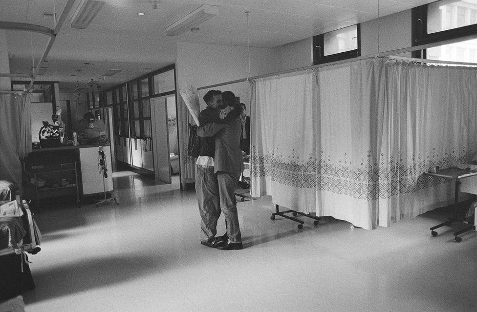 A pair hug in the hallway.