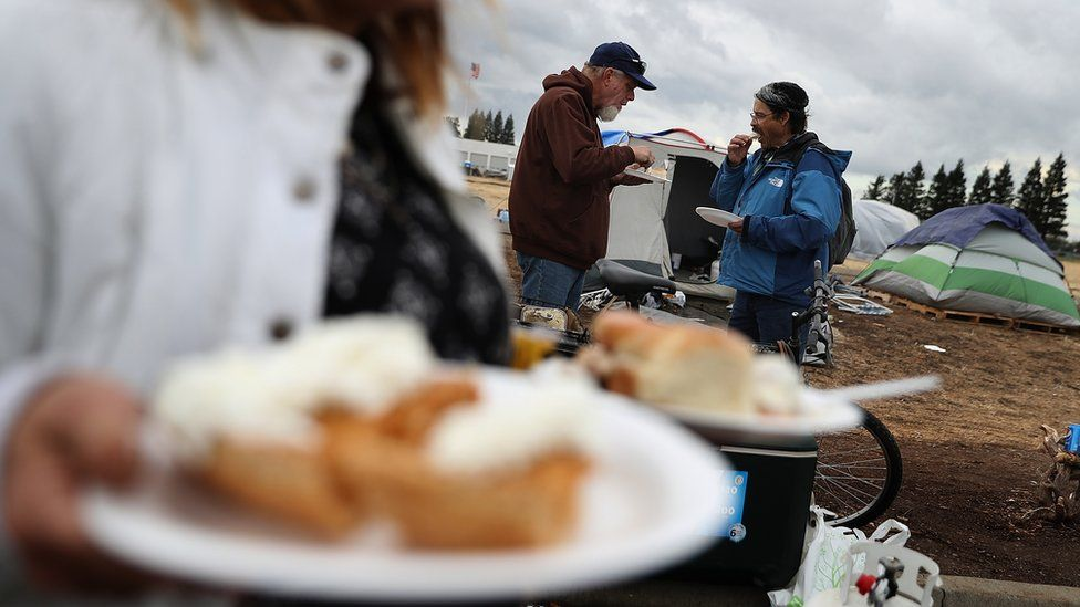 Camp Fire evacuees have a Thanksgiving meal in a makeshift evacuation camp next to a Walmart store in Chico, California, 22 November 2018