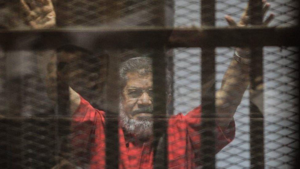 Ousted Egyptian President Mohamed Morsi gestures during a trial session on charges of espionage in Cairo, Egypt, 18 June 2016