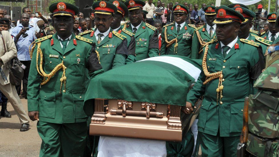 The bronze plated casket with the body of Odumegwu Ojukwu is being carried to his native Nnewi home by army pall bearers after a national inter-denominational funeral rites