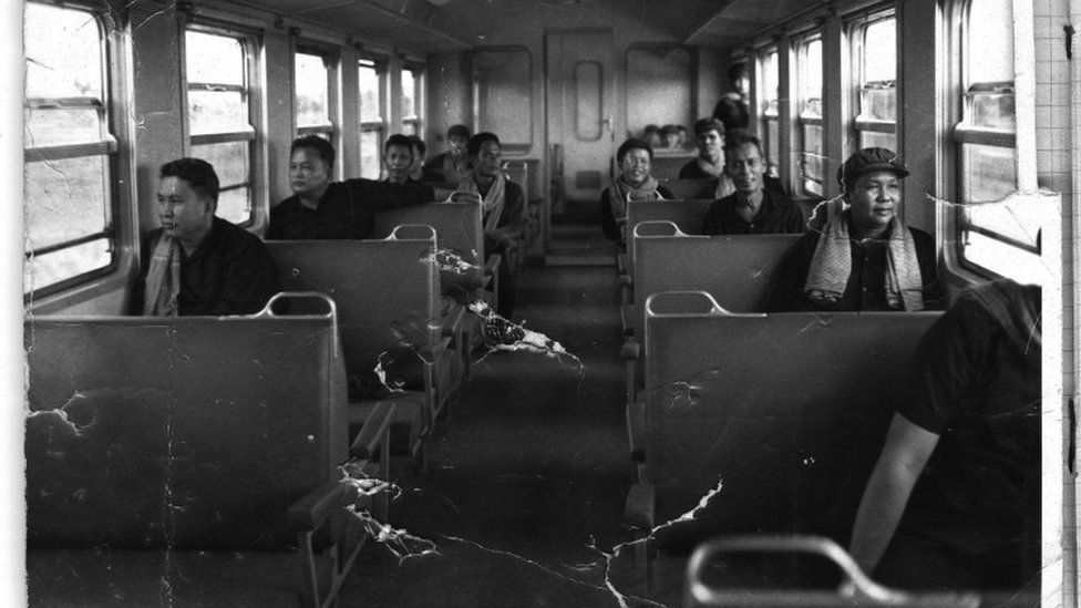 Pol Pot, front left, sits on a train in 1975, with Nuon Chea directly behind
