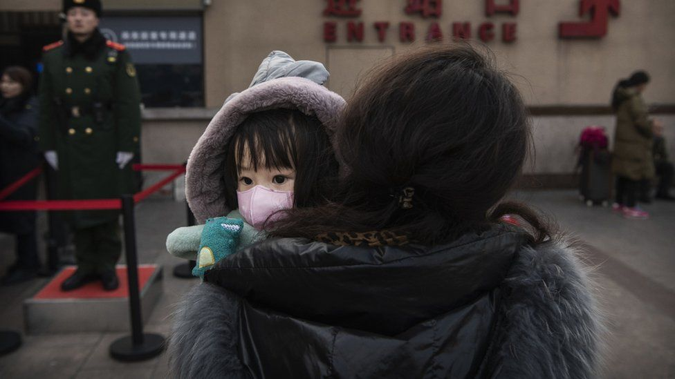 Child in Beijing wearing a protective mask, being carried by a relative