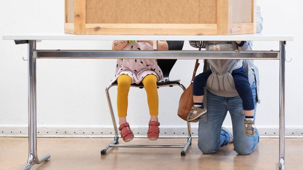 Woman with two young children votes in Berlin in the German federal election (26 September)