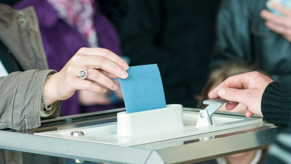 A woman's hand placing a ballot paper in a ballot box