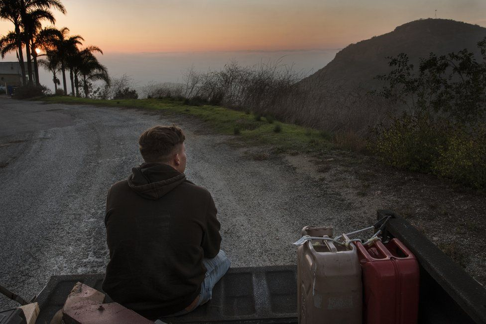Kase Dietrich sits on the tailgate of Brayden's 91 Chevy pickup, near Oceanside, LA