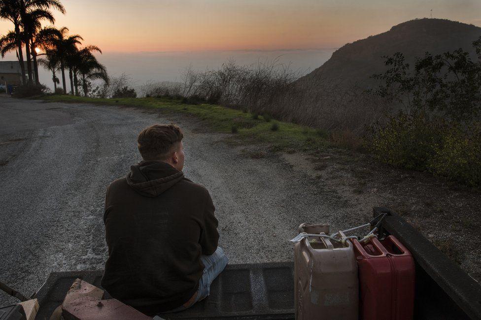 Kase Dietrich sits on the tailgate of Brayden's 91 Chevy pickup, near Oceanside, LA