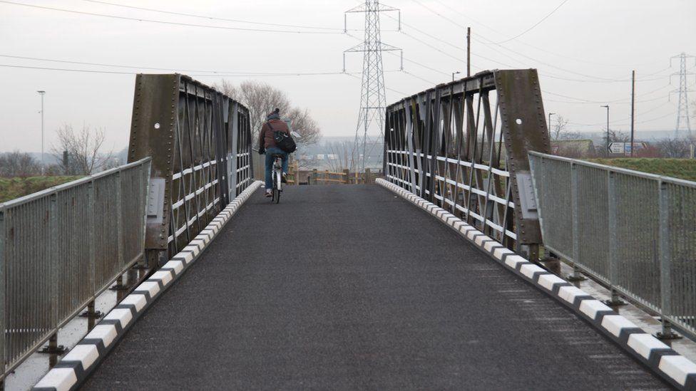 A cyclist on a bridge outside Fishlake