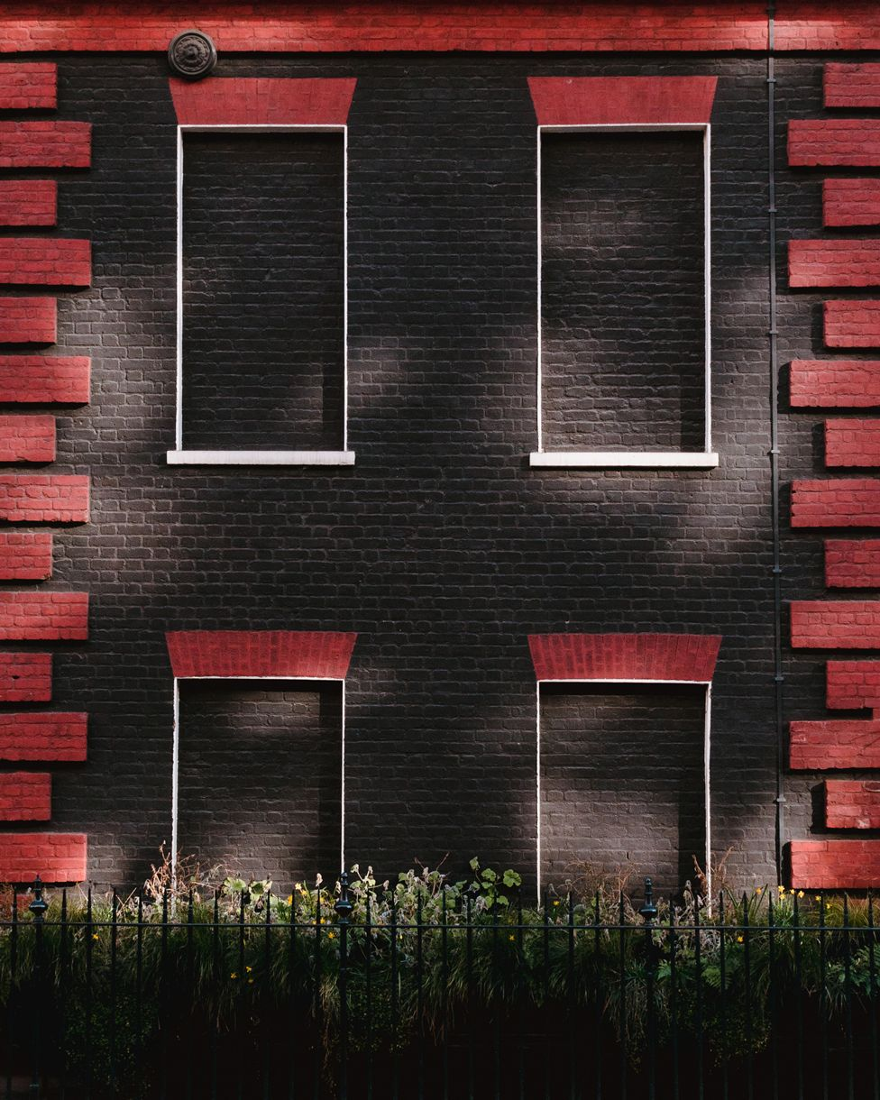 Four blocked windows on a building painted black and red, on Davies Street, London