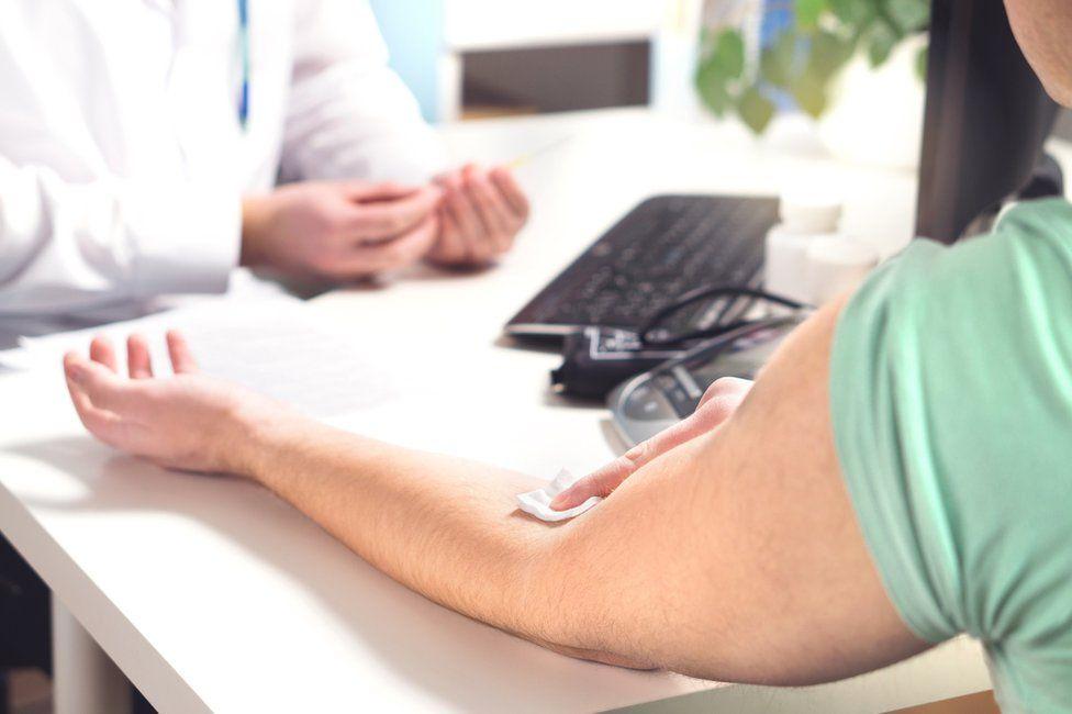 Man holding arm after blood test