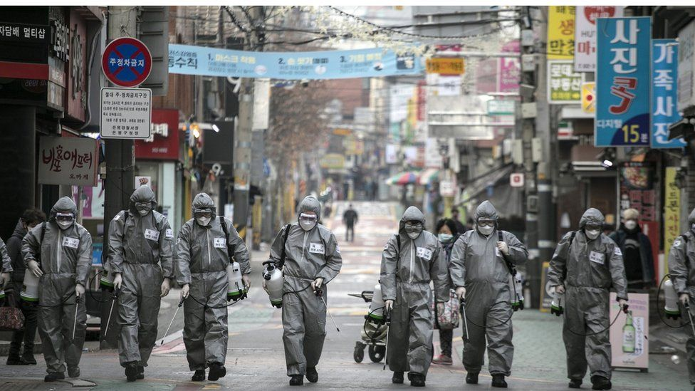 workers in South Korea disinfect a street