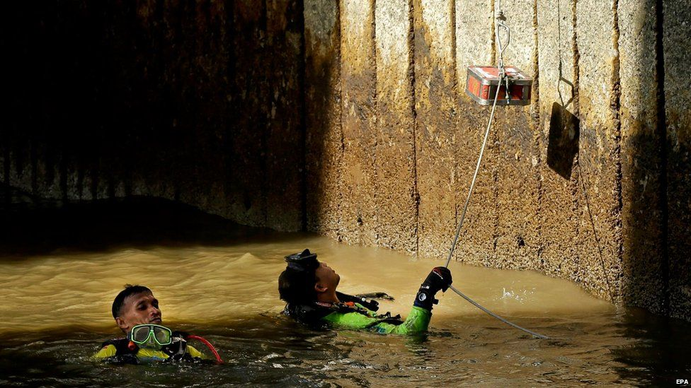 Divers retrieve and send up surviving pieces of an explosive device to be inspected at Sathorn pier, Bangkok, Thailand, on Tuesday after it was thrown towards the pier but exploded in the water without any casualties