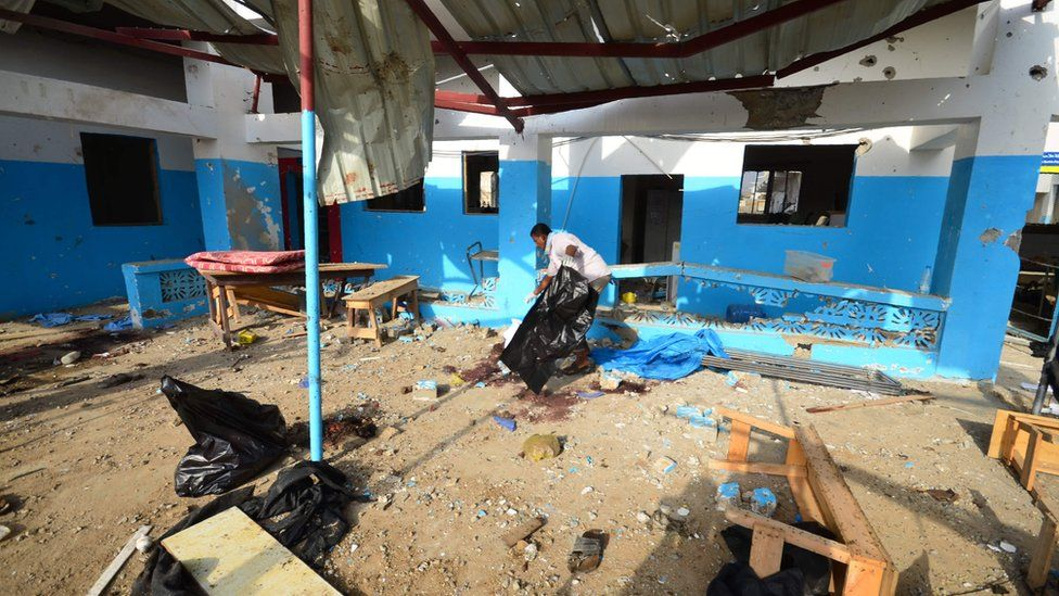 A Yemeni worker clears debris after the bombing
