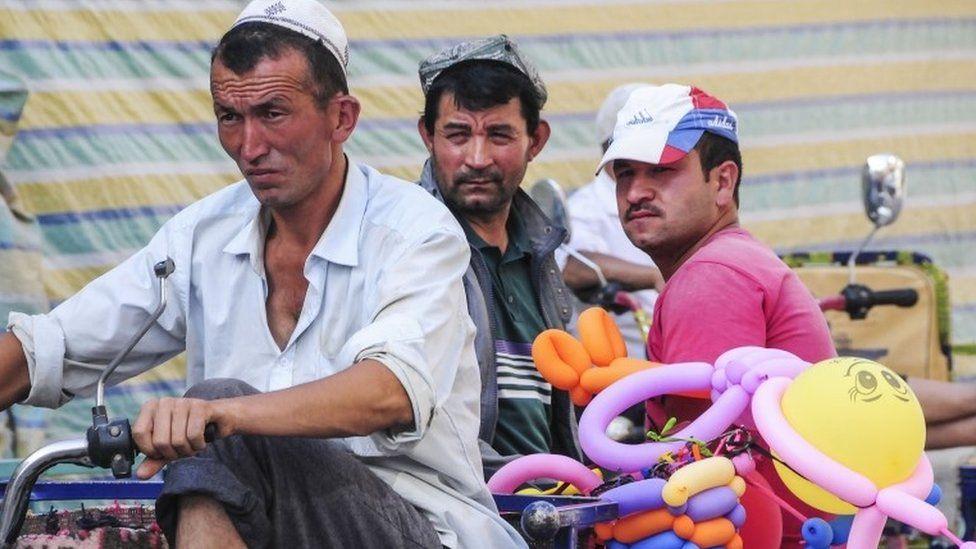 Uighur men on a vehicle in Xinjiang (file image