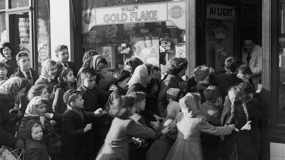 5th February 1953: A crowd of children rush to get into a sweetshop in north Acton as it opens its doors on the day sweet rationing ended.