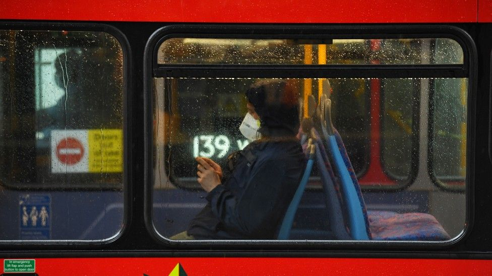 A commuter in a face mask on a London bus