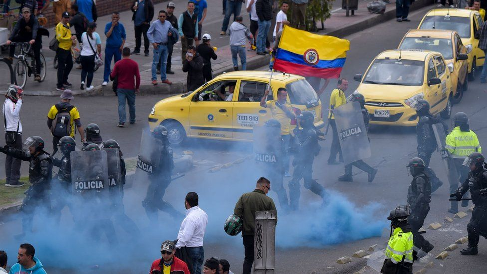 Police try to disperse taxi drivers amid protests against the private hire company Uber in Bogota, 23 October 2017