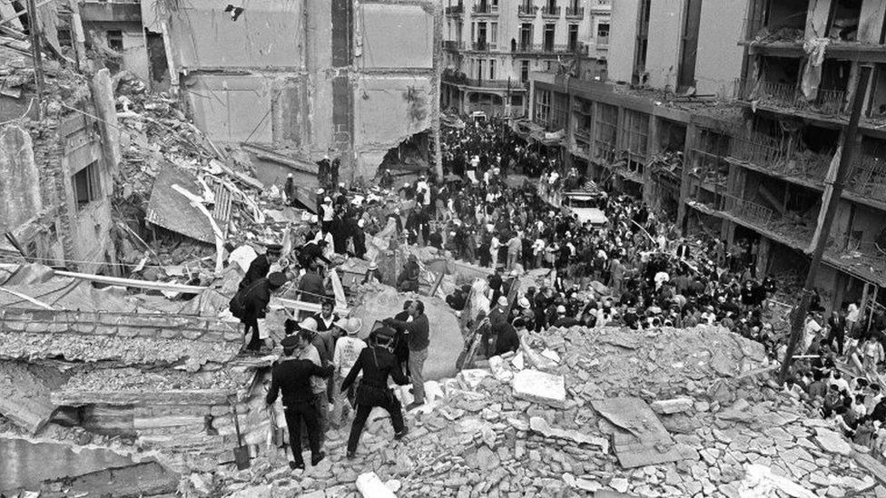 Firemen, policemen and rescuers search in rubble as a crowd looks on after a bomb exploded at the Israeli-Argentine Mutual Association (Amia) in Buenos Aires on 18 July 1994,