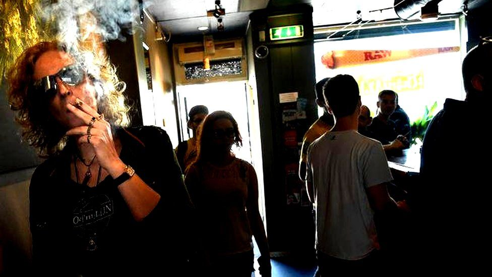 Customers smoke at the Toermalijn coffee shop in the Dutch city of Tilburg
