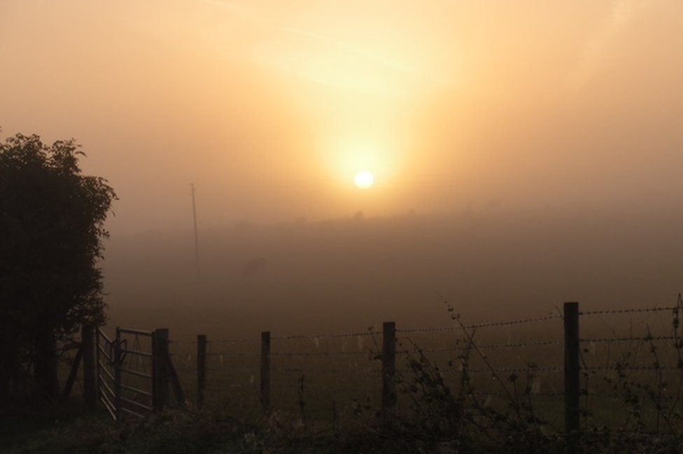 The sun shines through a misty sky in front of a field