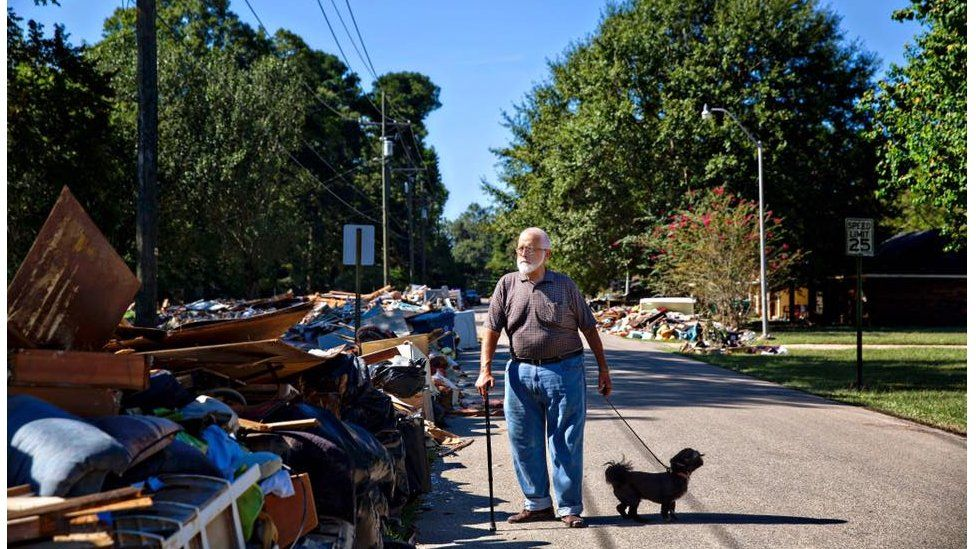 """Charles Tripp, of Rome, Georgia, walks Louie down his sister-in-law's street. He came down with family with an RV, supplies, and support. """"I am supervision, they're labor,"""" he remarks pointing to family members, """"I just had heart surgery."""" Denham Springs, LA."""