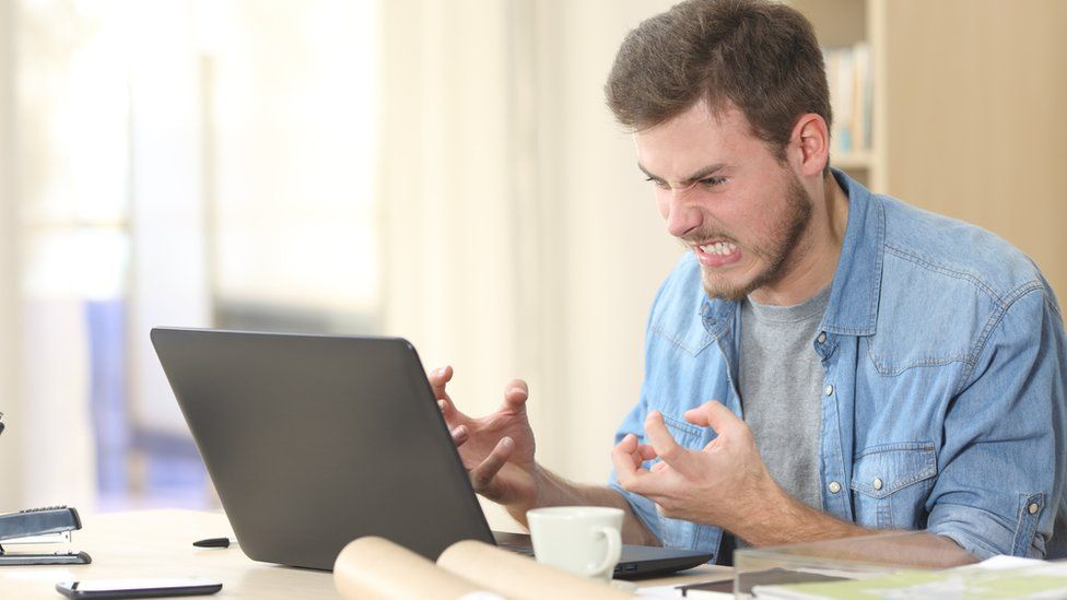 Frustrated man angry at laptop