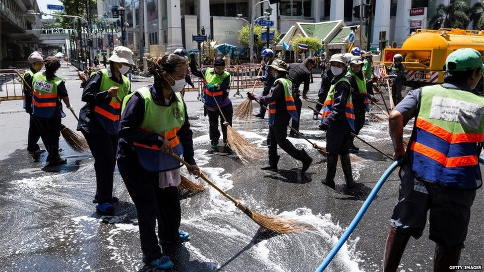 Workers clean up debris from the site of the explosion on 18 August 2015 in Bangkok, Thailand