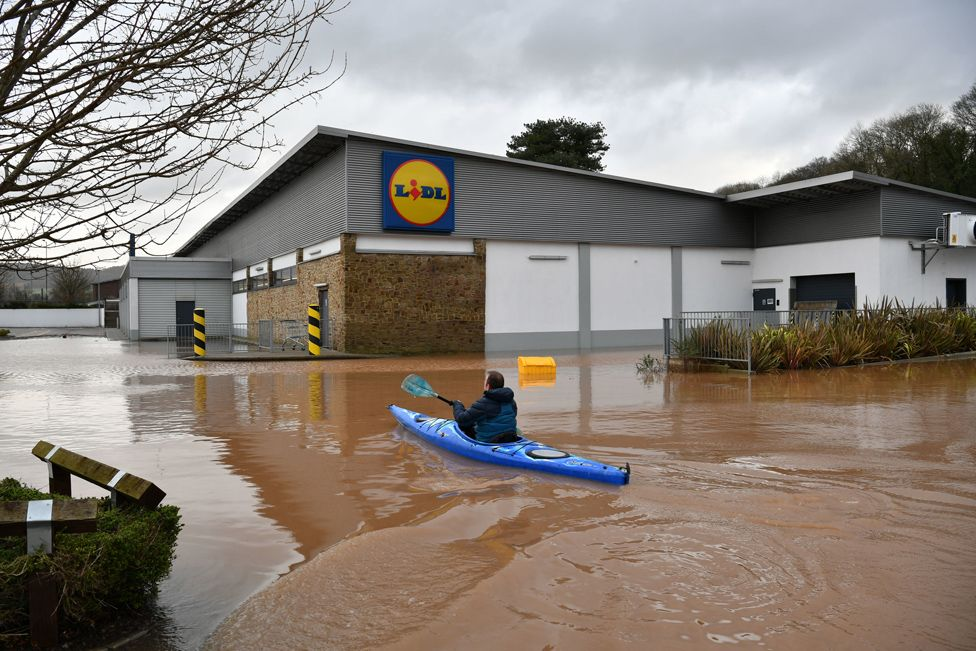 A canoeist makes their way past a flooded supermarket in Monmouth.