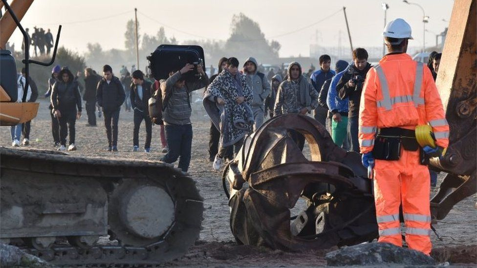 """Migrants walk by excavators and Members of the demolition crew in """"Jungle"""" migrant camp in Calais, northern France, on 27 October 2016"""
