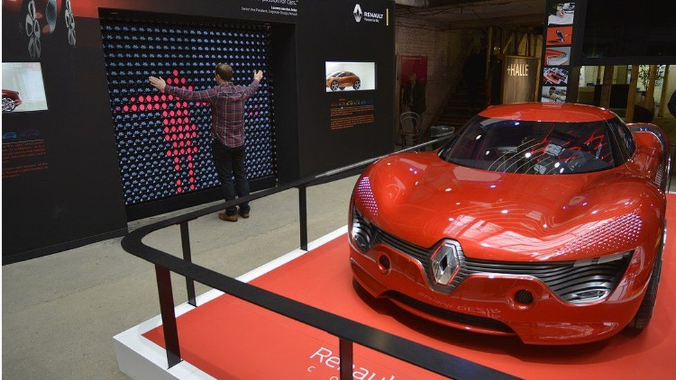 Renault Dezir electric car and man standing in front of light wall
