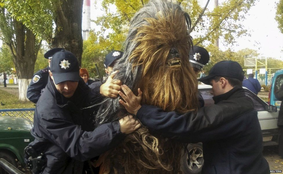 Policemen detain a person dressed as Star Wars character Chewbacca during a regional election near a polling station in Odessa, Ukraine,